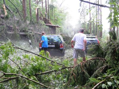 Zwei Autos stehen auf einer Straße bei Ecking (Landkreis Rosenheim, Oberbayern) zwischen umgestürzten Bäumen.