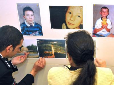 Polizeibeamte heften am 15.04.2011 vor der Pressekonferenz der SOKO Dennis Bilder von drei Opfern und deren Fundorte an eine Pinnwand.