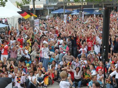 Fußballfans verfolgen den deutschen WM-Auftakt gegen Kanada auf der Fanmeile in Wolfsburg.