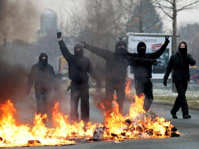 Autonome der linken Szene posieren am 19.02.2011 am Rande einer Neonazi-Kundgebung in Dresden hinter einer brennenden Barrikade.