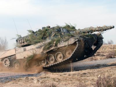Kampfpanzer vom Typ Leopard 2 in voller Fahrt auf einem Testgelände (Foto: Krauss-Maffei Wegmann)