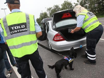 Dänische Zöllner kontrollieren am deutsch-dänischen Grenzübergang bei Froslev (Dänemark) ein Fahrzeug mit einem Spürhund.