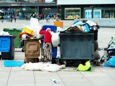 Frauen durchsuchen auf dem Alexanderplatz in Berlin Mülltonnen nach Pfandflaschen und anderem Nützlichen. Foto: Maurizio Gambarini/ Archiv