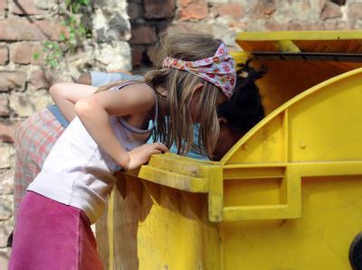 Zwei Kinder wühlen in Berlin-Kreuzberg in einer Mülltonne. Foto: Britta Pedersen/Archiv