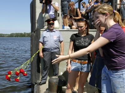 Eine Frau wirft Blumen in das Hafenwasser von Kazan: Russland trauert um die Opfer des schweren Schiffsunglücks auf der Wolga.