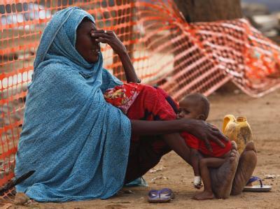 Eine verzweifelte Mutter mit ihrem unterernährten Kind.