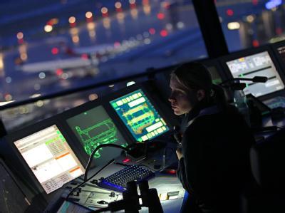 Eine Fluglotsin überwacht im Tower des Flughafens Düsseldorf den Luftverkehr. (Archivbild)
