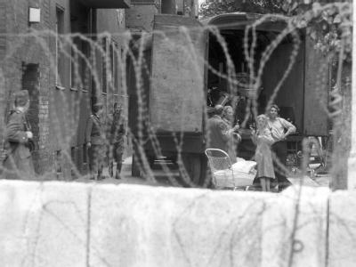 Während der Zwangsräumung von Häusern in der Bernauer Straße in Berlin 1961 wird eine Familie von Volkspolizisten der DDR  bewacht.