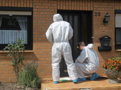 Mitarbeiter der Spurensicherung versiegeln nach der Beweissicherung ein Einfamilienhaus in Nindorf bei Stade.