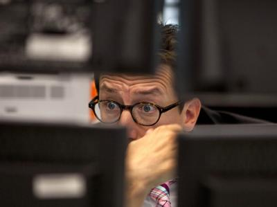 Ein Händler schaut in der Börse in Frankfurt am Main voller Sorge auf seine Monitore.