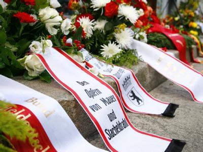 Blumen und Kränze liegen in der Zimmerstaße am Denkmal für das Maueropfer Peter Fechter. Peter Fechter wurde hier in der Nähe des Checkpoint Charlie beim Versuch die Mauer zu überwinden erschossen.