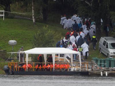 Angehörige der Opfer gehen auf der Fjordinsel Utöya in Norwegen.