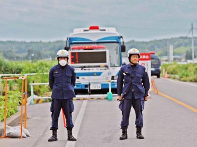 Polizisten bewachen eine Durchgangsstation zum Sperrgebiet um das AKW Fukushima.