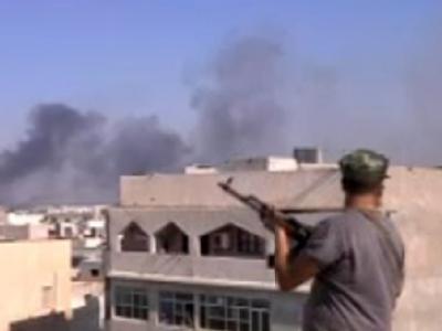 Ein Aufständischer in Tripolis. Im Hintergrund Rauchschwaden von den Gefechten um die Gaddafi-Residenz. (TV-Screenshot)