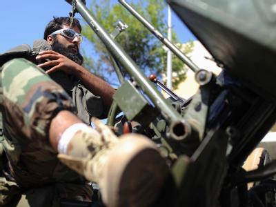 Ein Rebell sitzt auf einem Stützpunkt in Tripolis auf einem Pickup und warten auf einen Einsatz.