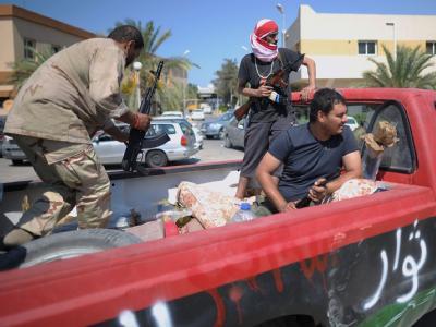 Rebellen sitzen auf einem Stützpunkt in Tripolis auf einem Pickup und warten auf ihren Einsatz.