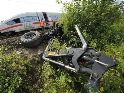 Trümmerteile des Treckers liegen neben den Bahngleisen. Bei der Kollision wurden zwei Menschen verletzt.