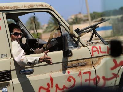 Ein Rebell fährt auf einer Zubringerstraße nach Tripolis.