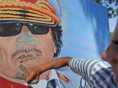 In Tripolis entlädt sich die Wut eines jungen Libyers auf das Porträt von Muammar al-Gaddafi.