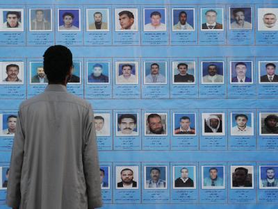 Ein Mann betrachtet am in Al-Sintan (Libyen) Bilder von Gefallenen oder Verschollenen.
