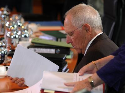 Bundesfinanzminister Wolfgang Schäuble (CDU) blättert zu Beginn der Sitzung des Bundeskabinetts im Kanzleramt in Berlin in Unterlagen.
