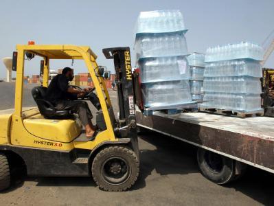 Trinkwasserflaschen werden in Tripolis abgeladen.