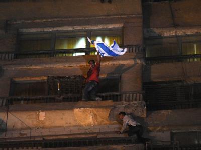 Hass auf den Nachbarn: Ein Demonstrant ist in Kairo an der Fassade des Botschaftsgebäudes hochgeklettert und hat die israelische Fahne heruntergerissen.