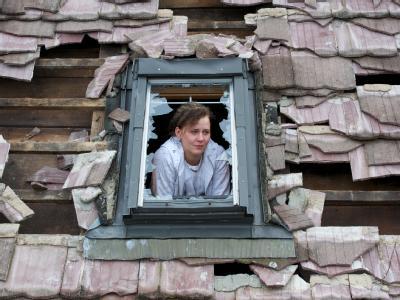 Eine Mutter schaut in Cörmigk (Salzlandkreis) aus dem zerstörten Fenster eines Kinderzimmers.