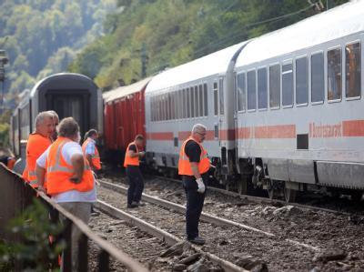 Bahnmitarbeiter schleppen den auf der Mittelrheinstrecke bei St. Goar entgleisten Personenzug aus dem Gleis.