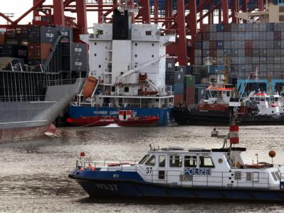 Einsatzkräfte versuchen in Hamburg, am Burchardkai das Containerschiff