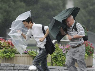 Zwei Männer kämpfen in Tokio mit ihren Regenschirmen gegen den Taifun Roke an.