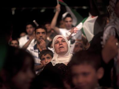In Ramallah verfolgt eine Palästinenserin die Ansprache von Mahmud Abbas vor den Vereinten Nationen.