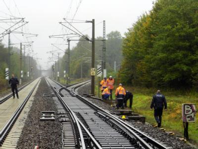Polizisten und Mitarbeiter der Deutschen Bahn untersuchen bei Falkensee ein Leitungskasten an den Bahngleisen. Foto: Holger Kohl