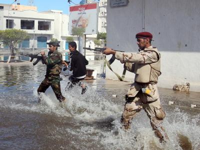 Schusswechsel auf einer überfluteten Straße in Sirte. Foto: Mohamed Messara