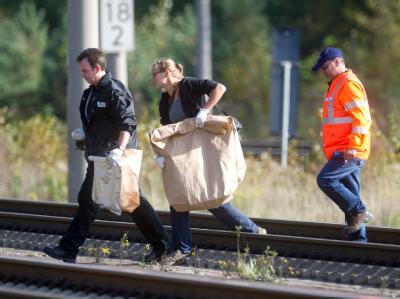Polizisten sichern in Berlin Beweismittel: In der Nähe des Bahnhofs Berlin Staaken sind weitere Brandsätze entdeckt worden. Foto: Tobias Kleinschmidt