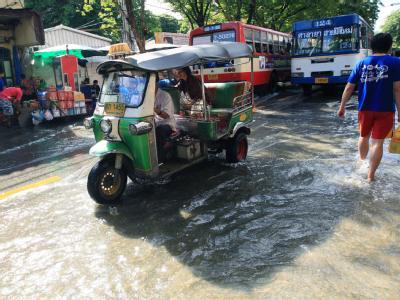 Das Wasser in den  Straßen von Bangkok hält den Verkehr nicht auf. Foto: Narong Sangnak