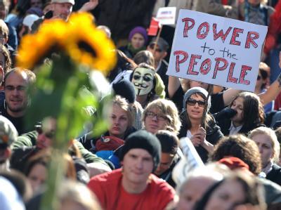 Demonstranten sitzen während einer Kundgebung vor der Europäischen Zentralbank in Frankfurt am Main. Foto: Arne Dedert