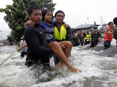 Thailändische Soldaten tragen eine Frau durch die Fluten. Foto: Rungroj Yongrit