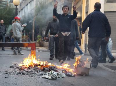 Ein Demonstrant neben einer brennenden Straßenbarrikade in Athen. Archivfoto: Friso Gentsch