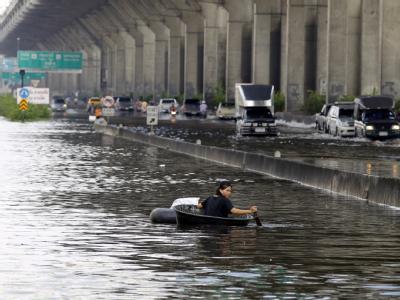 Eine Frau rudert in einer Wanne durch die überfluteten Straßen Bangkoks. Foto: Rungroj Yongrit, epa