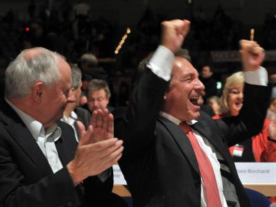 Der Vorsitzende der Partei Die Linke, Klaus Ernst (r) und der frühere Bundesvorsitzende Oskar Lafontaine freuen sich über das Abstimmungsergebnis. Foto: Martin Schutt, dpa