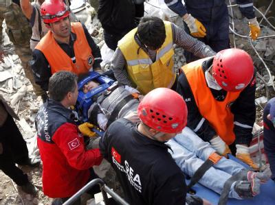 Rettungskräfte bergen einen verletzten Jungen aus den Trümmern, die das Erdbeben hinterlassen hat. Foto: Tolga Bozoglu
