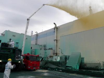 Arbeiter sprühen Staubbindemittel in das havarierte Atomkraftwerk Fukushima. Archivfoto: Tepco