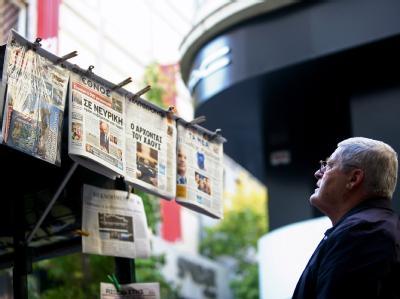 Ein Passant studiert die Zeitungsüberschriften an einem Kiosk in Athen. Sie stellt die Griechen vor die Wahl: Entscheidet euch, ob ihr im Euroland bleiben wollt. Foto: Alkis Konstantinidis