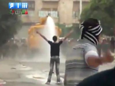 Das TV-Bild des Shaam News Network vom 17. Oktober zeigt einen syrischen Demonstranten vor einem Wasserwerfer, während ein weiterer Demonstrant im Vordergrund ein Stein wirft. Foto: Shaam News Network