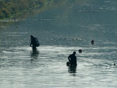 Taucher der Polizei suchen das Ufer des Elsterflutbetts in Leipzig ab. Foto: Peter Endig
