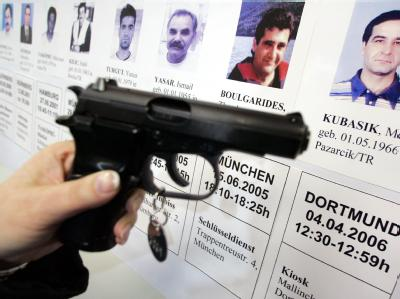 Eine mit der Mordwaffe baugleiche Pistole im Polizeipräsidium in Dortmund vor Porträts von Opfern der so genannten Döner-Morde. Archivfoto: Bernd Thissen