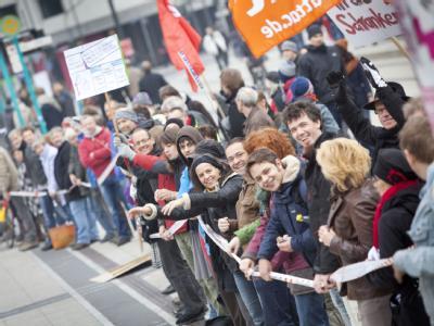 Demonstranten bilden in Frankfurt am Main eine Menschenkette rund um das Bankenviertel. Foto: Frank Rumpenhorst