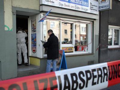 Polizeibeamte untersuchen nach einem Mord in Dortmund einen Kiosk auf Spuren am 04.04.2006. Foto: Nils Foltynowicz