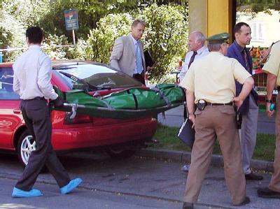 Mitarbeiter eines Bestattungsunternehmens transportieren am 29.08.2001 im Münchner Vorort Ramersdorf die Leiche eines ermordeten 38-jährigen Mannes ab. Archivfoto: Reinhard Kurzendörfer